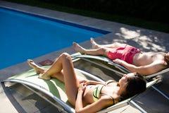 Par som kopplar av på vardagsrumstol på poolsiden Royaltyfria Foton