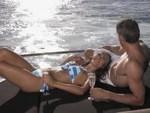 Par som kopplar av på yachts kant Arkivfoton