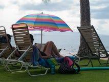 Par som kopplar av under det färgrika paraplyet Royaltyfri Bild