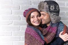 par som kramar att älska slitage vit vinter för härlig stående för begreppsklänningflicka Arkivfoto
