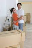 Par som kramar i nytt hus Fotografering för Bildbyråer