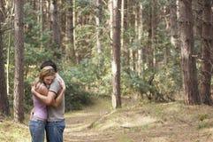 Par som kramar i skog royaltyfri foto