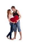 Par som kramar med en röd hjärta Royaltyfria Bilder