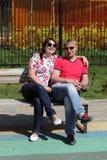Par som kramar på en bänk Arkivbild