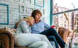 Par som kramar på en soffa royaltyfria foton