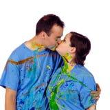 Par som kysser after att ha ett målarfärgslagsmål Arkivfoto
