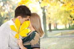 Par som kysser bak den stora leafen Arkivbilder