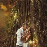 Par som kysser i mystisk skog Arkivfoto