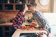Par som kysser, medan förbereda en romantisk matställe arkivfoton