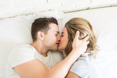 Par som kysser, medan ligga i säng fotografering för bildbyråer