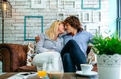 Par som kysser på en soffa fotografering för bildbyråer