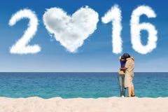 Par som kysser på stranden med nummer 2016 arkivbilder