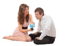 Par som leker med ett geografiskt jordklot arkivbilder
