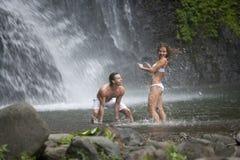 par som leker under vattenfall Royaltyfria Bilder