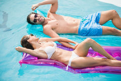 Par som ler, medan koppla av på den uppblåsbara flotten Arkivfoton