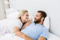 Par som ler, medan koppla av på säng Fotografering för Bildbyråer