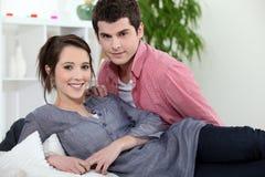 Par som lägger på soffan Arkivbilder