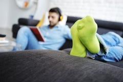Par som ligger på den Sofa With Tablet PC:N och hörlurar Fotografering för Bildbyråer