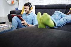 Par som ligger på den Sofa With Tablet PC:N och hörlurar Arkivfoton