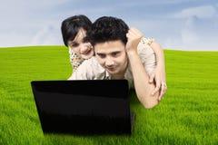 Par som ligger på gräs som ser bärbara datorn Arkivfoto