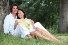 Par som ligger på gräset Royaltyfri Fotografi
