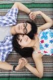 Par som ligger på picknickfilten Arkivbilder
