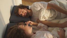 Par som ligger på sängen som ser de stock video