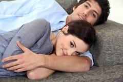 Par som ligger på soffan royaltyfria foton