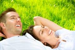 Par som ligger på gräs Arkivbilder