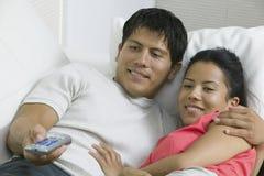Par som ligger på soffan med fjärrkontroll Royaltyfria Bilder