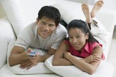 Par som ligger på soffan med fjärrkontroll Fotografering för Bildbyråer