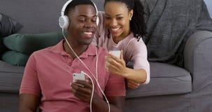 Par som lyssnar till musik och tar bilden med smarta telefoner Arkivfoton