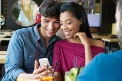 Par som lyssnar till musik på stången arkivbilder