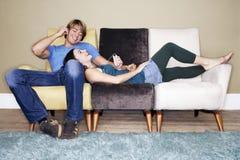 Par som lyssnar till spelaren MP3 på soffan Arkivbilder