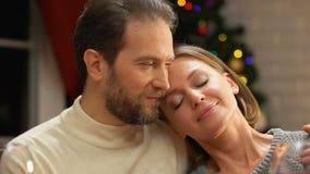 Par som omfamnar försiktigt på julaftonen, kvinna som gör önskaen, festligt mirakel lager videofilmer