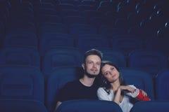Par som omfamnar i bio och hållande ögonen på film Royaltyfria Foton