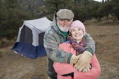 Par som omfamnar i Front Of Camping Tent Arkivbilder