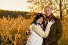 Par som omfamnar i höstbygdsolnedgång royaltyfri foto