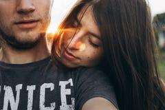 Par som omfamnar i sommarsolnedgång hållande huvud för kvinna på hennes man royaltyfri fotografi