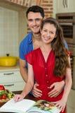 Par som omfamnar, medan kontrollera receptboken Arkivfoton