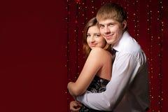 Par som omfamnar mot bakgrunden av lampor Royaltyfri Bild