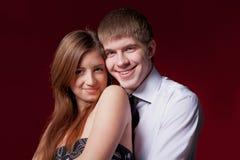 Par som omfamnar på den röda bakgrunden Fotografering för Bildbyråer