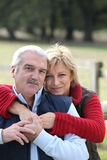 par som omfamnar pensionären Arkivfoton