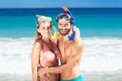 Par som omfamnar sig på stranden Arkivbild