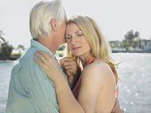 Par som omfamnar vid floden Royaltyfri Foto
