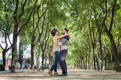 Par som omfamnas i parkera av Maria Luisa i Seville fotografering för bildbyråer