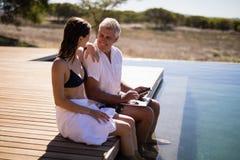 Par som påverkar varandra, medan genom att använda bärbara datorn nära poolside Royaltyfri Foto
