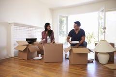 Par som packar upp askar i nytt hem på rörande dag royaltyfri foto