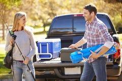 Par som packar upp, väljer upp lastbilen på campa ferie Arkivbild