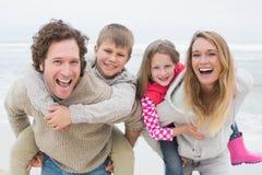 Par som piggybacking ungar på stranden Fotografering för Bildbyråer